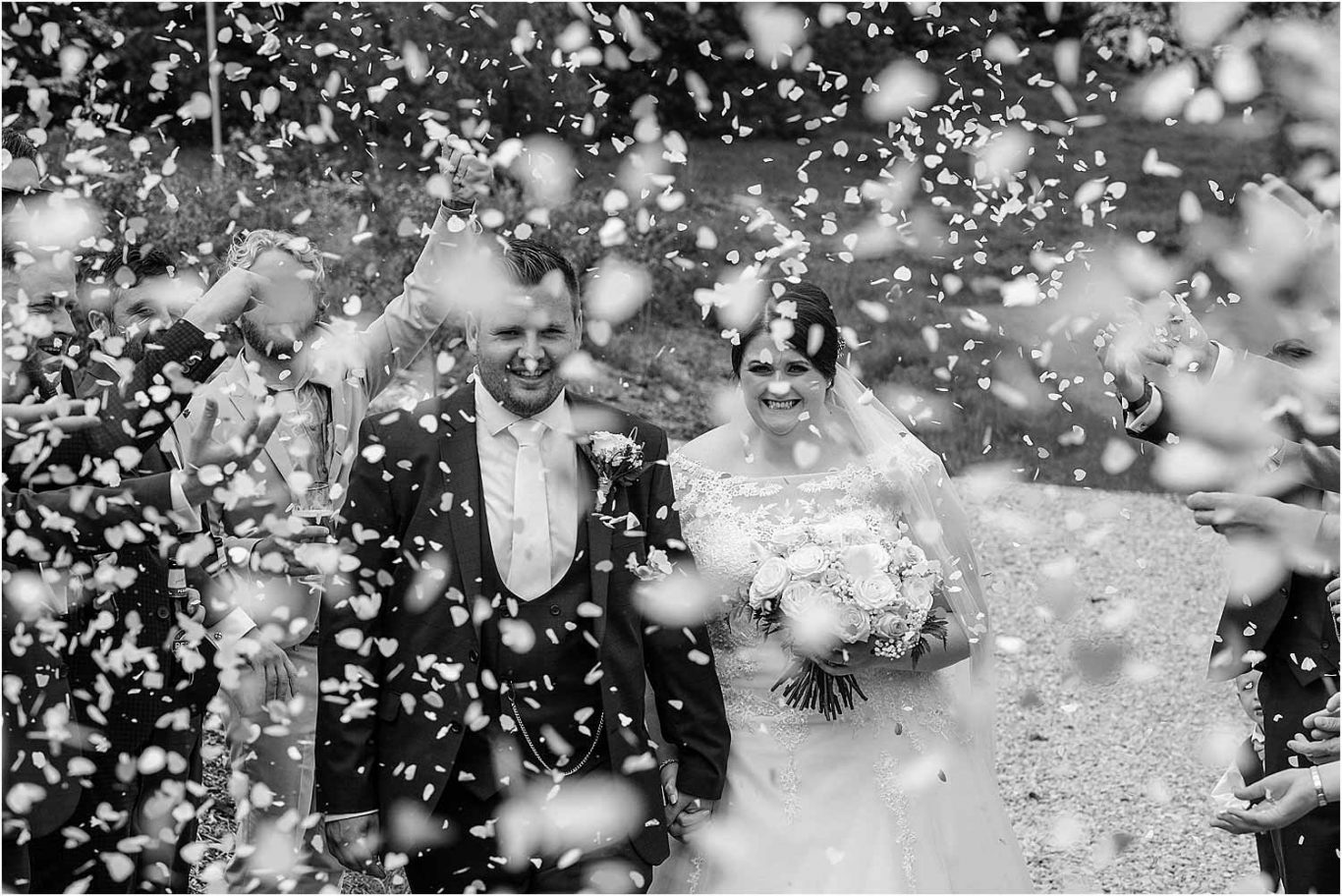 brdie and groom lost amongst confetti