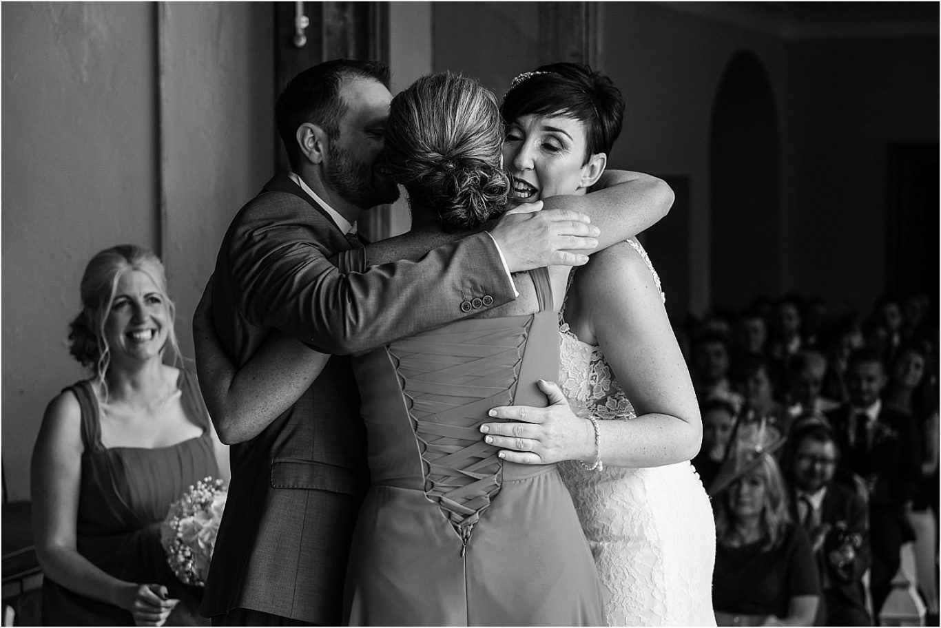 bride and groom hugging a guest