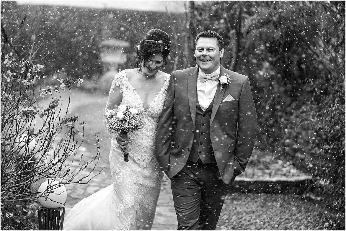 bride and groom walking in snow shower